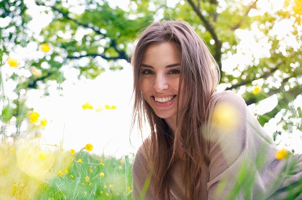 Mujer joven sobre el pasto sonriendo