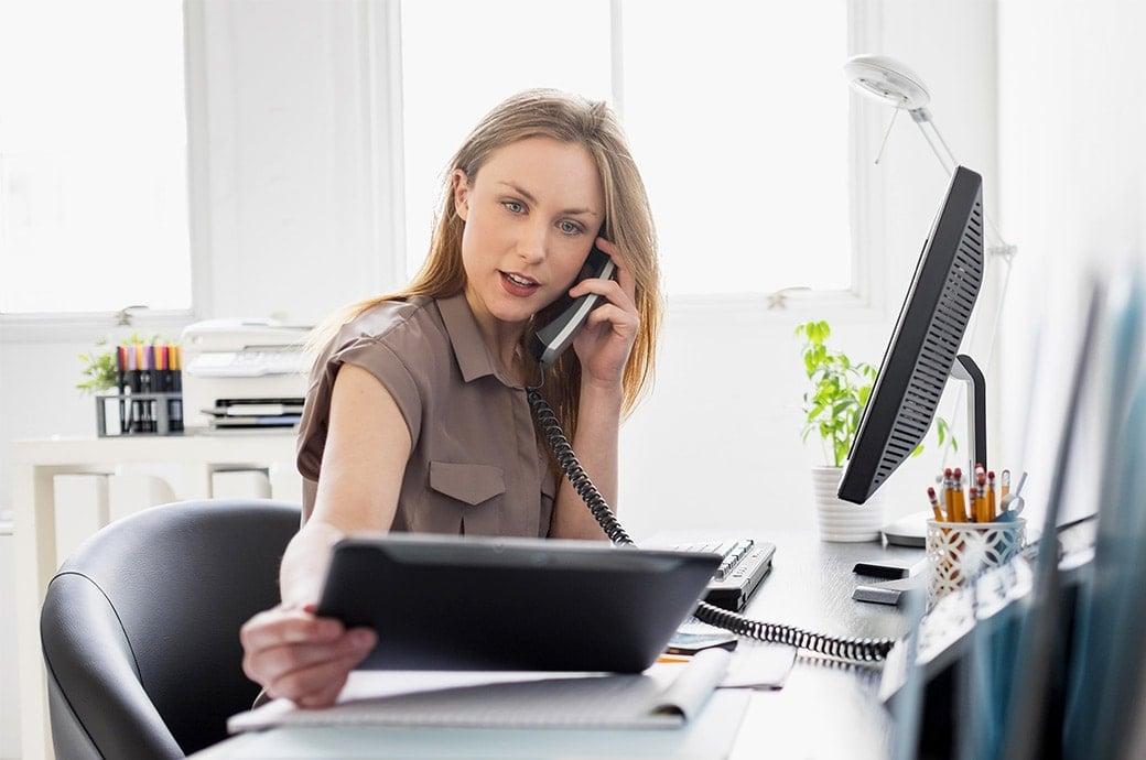 Mujer en su escritorio mirando una tablet