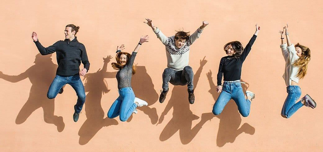 Amigos saltando en el aire con manos arriba