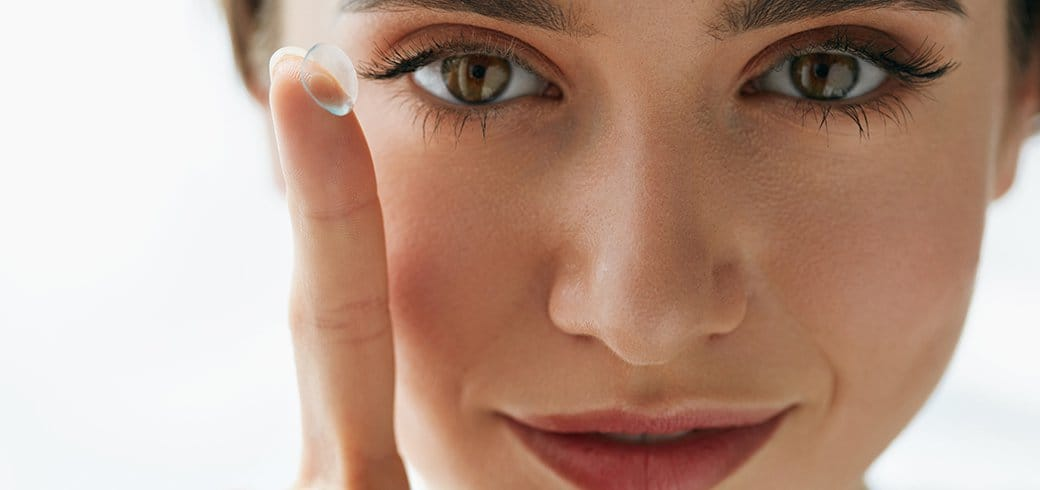 Mujer con lente de contacto en los ojos a punto de ponerselo