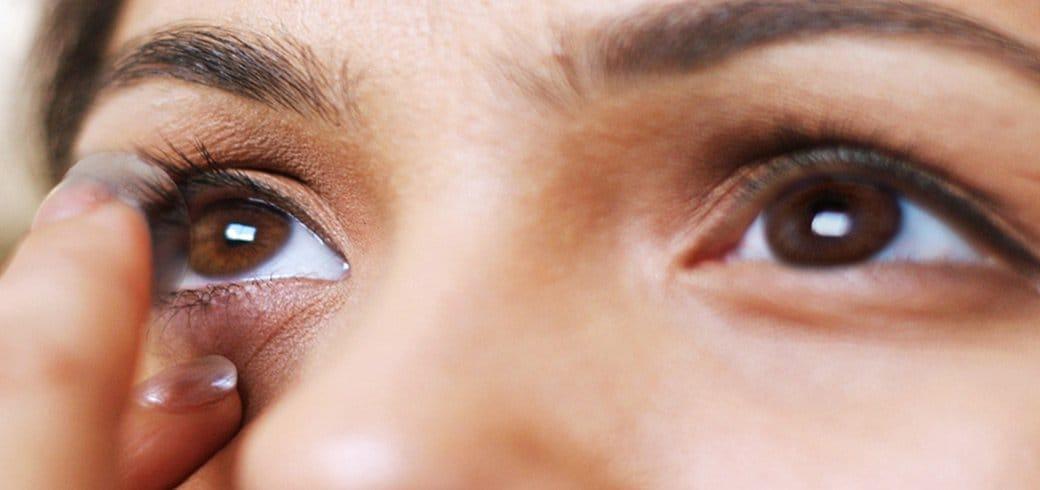 Acercamiento de una mujer en espejo poniéndose lentes de contacto